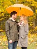Uśmiechnięta para z parasolem w jesień parku Obrazy Royalty Free