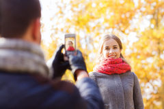 Uśmiechnięta para z smartphone w jesień parku Obrazy Stock