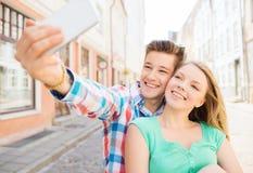 Uśmiechnięta para z smartphone w mieście Zdjęcia Stock