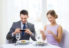 Uśmiechnięta para z zakąskami i smartphones Fotografia Stock
