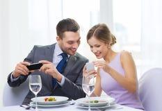Uśmiechnięta para z zakąskami i smartphones Fotografia Royalty Free