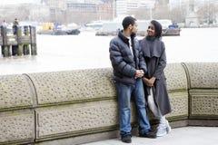 Uśmiechnięta pary pozycja na moscie, patrzeje each inny Obrazy Stock