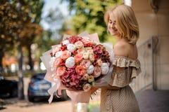 Uśmiechnięta piękna dziewczyna trzyma bukiet namiętni kwiaty Obrazy Stock