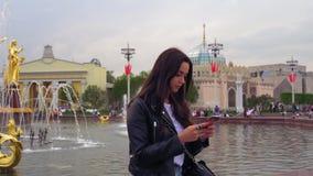 Uśmiechnięta piękna dziewczyna ubierał w modnej czarnej kurtce U?ywa smartphone zdjęcie wideo