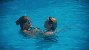 Uśmiechnięta piękna kobieta i jej śliczny dziecko w basenie Macierzysty uczenie pływać jej małej córki zbiory