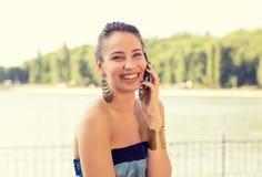 Uśmiechnięta piękna kobieta opowiada na telefonie komórkowym outdoors jeziorem fotografia stock
