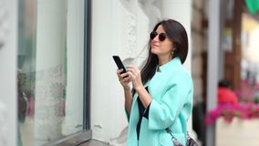 Uśmiechnięta piękna kobieta podziwia brać fotografię szkło sklepu gablota wystawowa używać smartphone zbiory