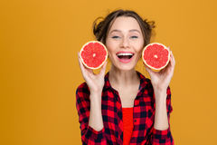 Uśmiechnięta piękna kobieta trzyma dwa połówki grapefruitowy Obrazy Stock