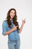 Uśmiechnięta piękna młoda kobieta stoi i wskazuje strona Fotografia Royalty Free