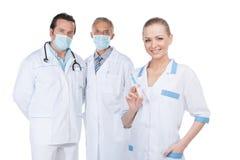 Uśmiechnięta piękna pielęgniarka na przedpolu z strzykawką. fotografia stock