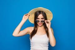Uśmiechnięta piękno młoda kobieta z okularami przeciwsłonecznymi i kapeluszem w nowożytnym stylu na tle błękitna ściana Obrazy Stock
