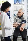 Uśmiechnięta pielęgniarka Sprawdza Cierpliwego ` s ciśnienie krwi Zdjęcie Royalty Free