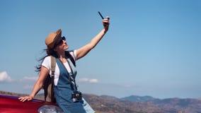 Uśmiechnięta podróży kobieta z falowanie włosy pozuje na samochodowej czapeczce bierze selfie używać smartphone zbiory