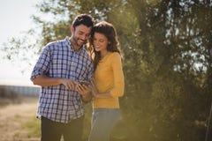 Uśmiechnięta potomstwo para używa telefon komórkowego przy oliwki gospodarstwem rolnym zdjęcie stock