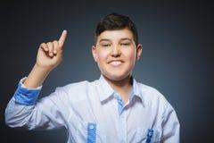 Uśmiechnięta preteen chłopiec z dobrymi pomysłów chwytami dotyka up na szarym tle zdjęcia stock