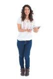 Uśmiechnięta przypadkowa brunetka używać jej pastylka komputer osobistego Zdjęcie Royalty Free