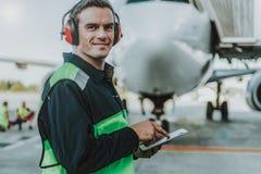 Uśmiechnięta przystojna pracownik pozycja przed ogromnym samolotem obraz stock