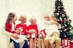 Uśmiechnięta rodzina ściska w domu z prezentami Zdjęcia Stock