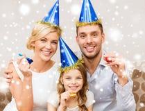 Uśmiechnięta rodzina dmucha przysługę w błękitnych kapeluszach uzbrajać w rogi obraz stock