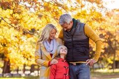 Uśmiechnięta rodzina przy parkiem podczas jesieni Zdjęcie Stock