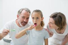 Uśmiechnięta rodzina szczotkuje ich zęby z toothbrush Fotografia Stock