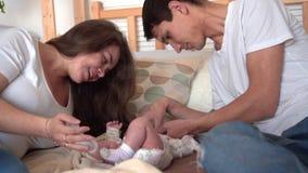 Uśmiechnięta rodzina w łóżku dotyka i opowiada z ich dziecko córką, dokąd tata i mama jesteśmy oglądający zbiory wideo
