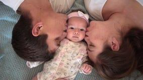 Uśmiechnięta rodzina w łóżku, rodzice delikatnie całuje ich dziecka dokąd chłodno twarz plan jest tatą, mamą i małym córką, zbiory wideo