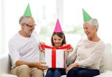 Uśmiechnięta rodzina w partyjnych kapeluszach z prezenta pudełkiem w domu Zdjęcie Royalty Free