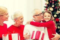 Uśmiechnięta rodzina z prezentami w domu Fotografia Stock