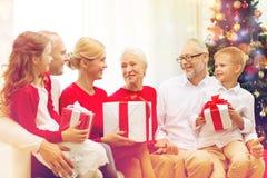 Uśmiechnięta rodzina z prezentami w domu Zdjęcie Royalty Free