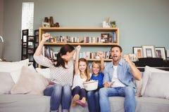 Uśmiechnięta rodzina z rękami podnosić podczas gdy oglądający telewizję Zdjęcia Stock