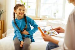 Uśmiechnięta rozochocona ładna dziewczyna trzyma jej rękę na brzuszku zdjęcie stock