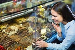 Uśmiechnięta rozochocona dziewczyna wybiera wyśmienicie czekolady i ganaches obrazy stock