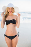Uśmiechnięta seksowna blondynka jest ubranym słomianego kapelusz w eleganckim bikini Obraz Royalty Free