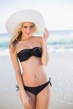 Uśmiechnięta seksowna blondynka jest ubranym słomianego kapeluszu pozować w eleganckim bikini Zdjęcie Stock