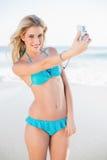 Uśmiechnięta seksowna blondynka w bikini bierze jaźń obrazek Zdjęcia Royalty Free