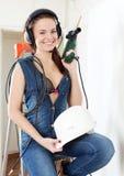 Uśmiechnięta seksowna dziewczyna w hełmofonach z świderem i hardhat zdjęcie stock