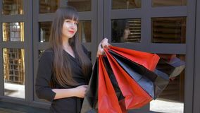 Uśmiechnięta shopaholic dziewczyna podczas czarnego Piątku cieszy się weekendowego zakupy z udziałem papierowe torby w rękach zbiory wideo