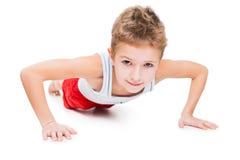 Uśmiechnięta sporta dziecka chłopiec prasa up ćwiczy Obraz Royalty Free