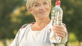 Uśmiechnięta sportsmenka seansu butelka woda i aprobaty, opieka zdrowotna, aktywność zbiory wideo