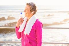 Uśmiechnięta sporty kobieta słucha muzyka z bidonem fotografia stock