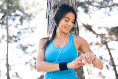 Uśmiechnięta sporty kobieta używa mądrze zegarek fotografia royalty free