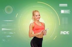 Uśmiechnięta sporty kobieta z smartphone zdjęcia stock