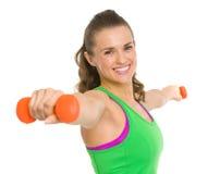 Uśmiechnięta sprawności fizycznej młoda kobieta robi ćwiczeniu z dumbbells Zdjęcia Royalty Free