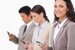 Uśmiechnięta sprzedawczyni z telefonem komórkowym obok kolegów Obrazy Stock