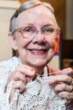 Uśmiechnięta stara kobieta z Szydełkowym obrazy royalty free