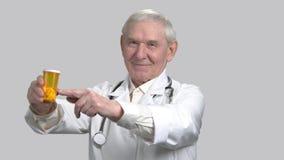 Uśmiechnięta stara senior lekarka z pigułką może up i kciuk zbiory