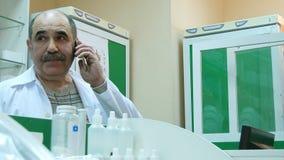 Uśmiechnięta starsza farmaceuta na telefonie w aptece Obrazy Royalty Free