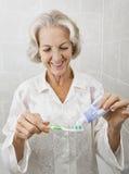 Uśmiechnięta starsza kobieta gniesie pasta do zębów na toothbrush w łazience Zdjęcie Stock