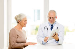 Uśmiechnięta starsza kobieta i lekarka z pastylka komputerem osobistym Fotografia Royalty Free
